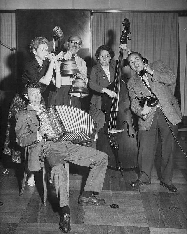 Schwarz-weiss Foto mit zwei Frauen und drei Männern, die fröhlich musizieren.