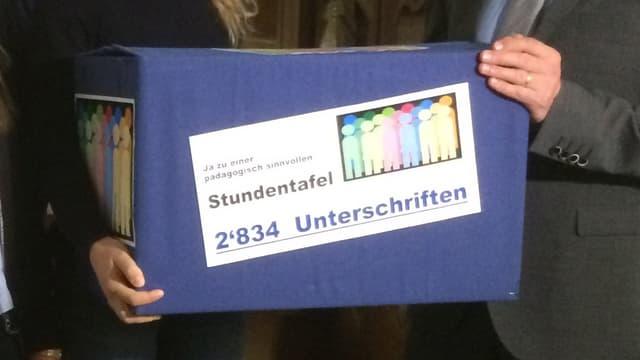 Blick auf den Karton mit den Unterschriften, wo geschrieben steht, dass 2834 Unterschriften gesammelt wurden