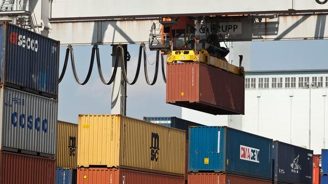 Blick auf eine Cargo-Verladestation. Ein Container hängt an einem Kran in der Luft.