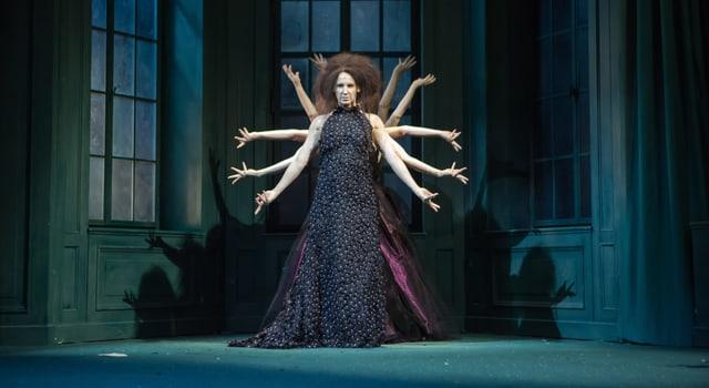Eine Frau steht auf der Theaterbühne, hinter hier viele andere Frauen, von denen man nur die Arme sieht.