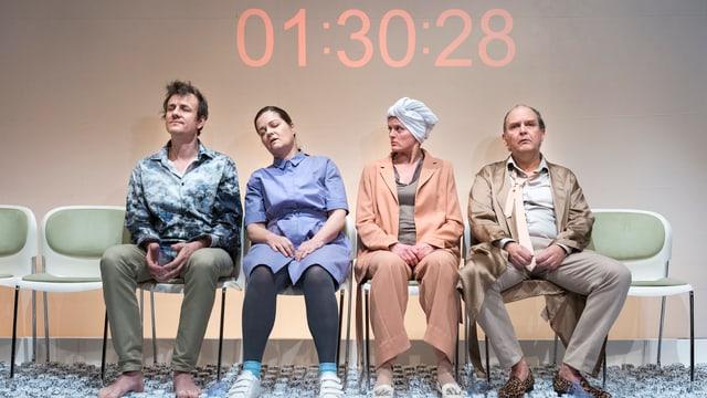 Szene mit zwei Frauen und zwei Männern die auf einer Wartebank sitzen. Im Hintergrund an der Wand ein Countdown.