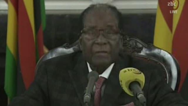 Um che sesa vi dad ina maisa cun in microfon davant el.