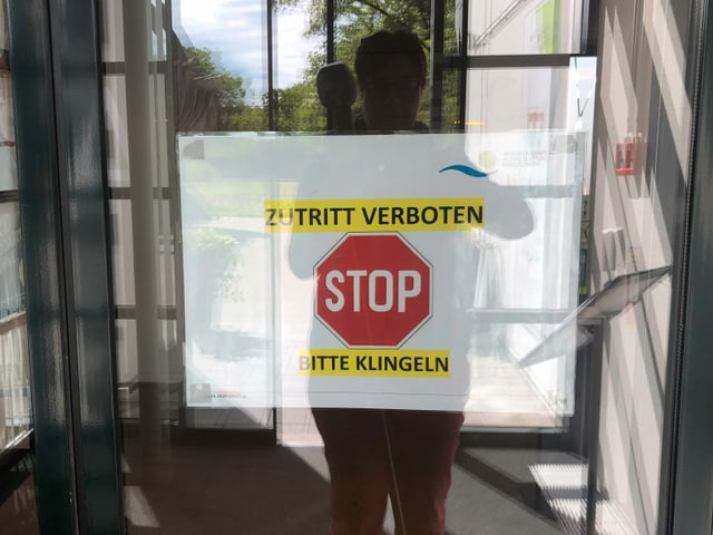 Eine Person steht vor einer verschlossenen Glastüre mit der Aufschrift STOPP.