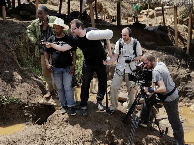 Fünf Männer zwei mit Filmequipement stehen auf Lehmboden. Hintergund Hütten.