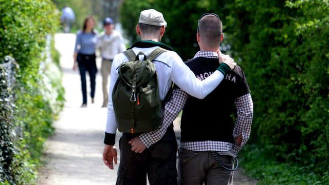 Zwei Männer spazieren Arm in Arm.