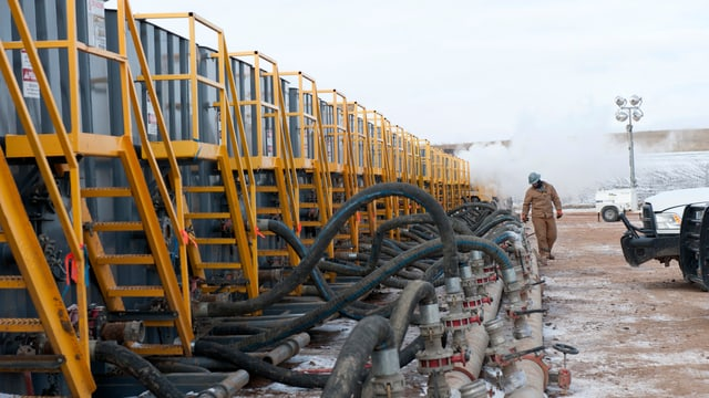 Ein Mann in Arbeitskleidung kontrolliert Schläuche und Leitungen einer Ölförderanlage