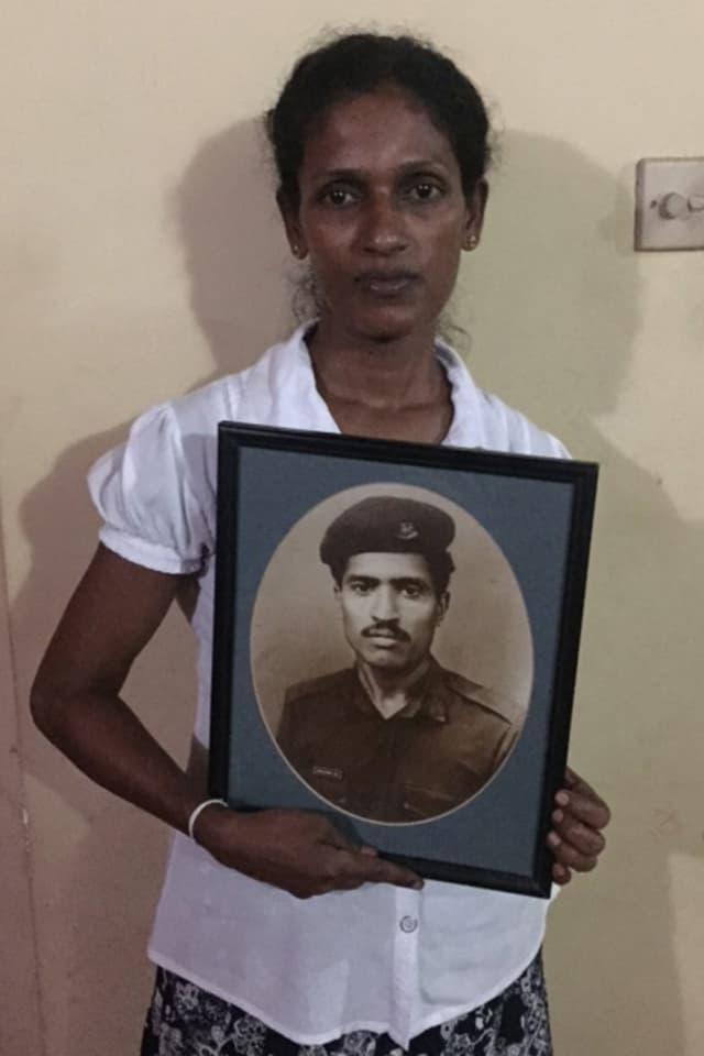 Eine Kriegswitwe hält das Bild ihres verstorbenen Mannes in den Händen.