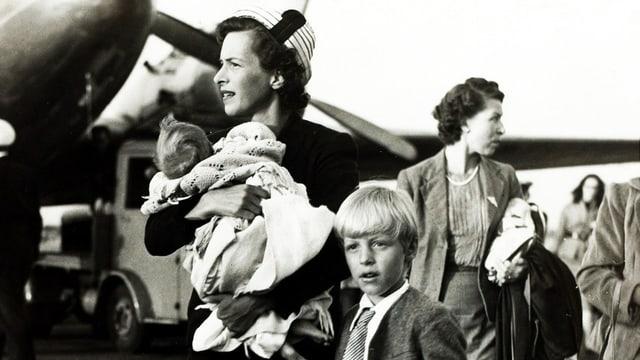 Frau mit Kindern auf Flugfeld