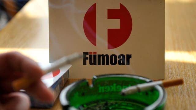Ein grüner Aschenbecher mit einer brennenden Zigarette, dahinter ein weisses Schild mit der Aufschrift Fümoar.