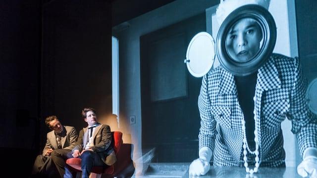 """Photo aus der Probe der Produktion """"Kino Marie"""": zwei Männer sitzen auf roten Kinosesseln und betrachten ein älteres Bild einer Kundin an der Kinokasse."""