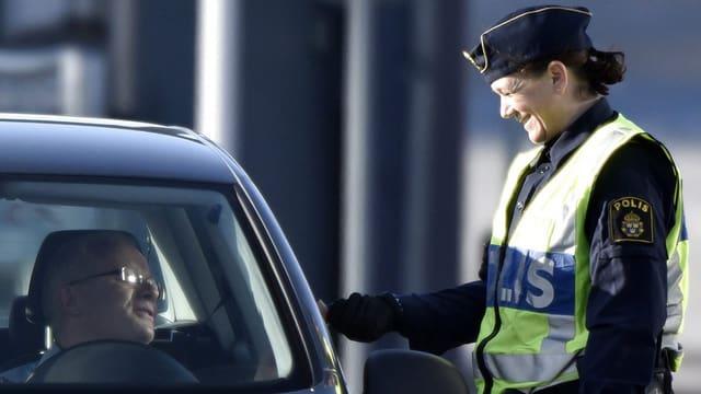 Eine schwedische Beamtin kontrolliert einen Einreisenden in Lernacken.
