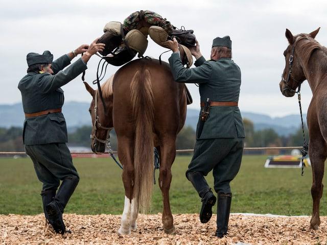 Zwei Soldaten in alten Armeeuniformen satteln ein Pferd.