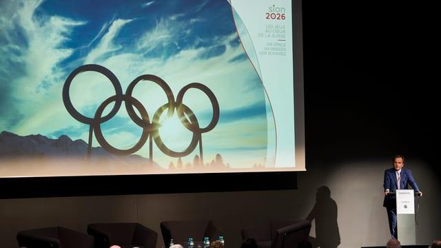 Eine Leinwand mit den olympischen Ringen, daneben Jean-Philippe Rochat.