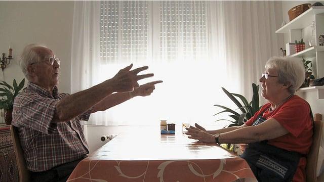 Ein älteres Ehepaar diskutiert am Tisch.
