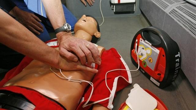 Scolaziun cun ina poppa da duvrar in defibrilatur.