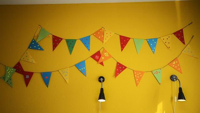 Die farbige Girlande an der gelben Wand ist von Lennie und Lauri selbstgemacht.