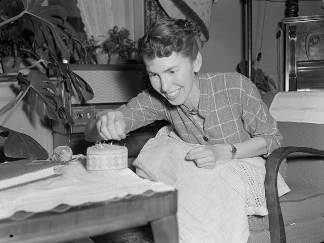 Schwarz-Weiss-Fotografie mit einer Frau, die auf einem Stuhl sitzt und stickt.