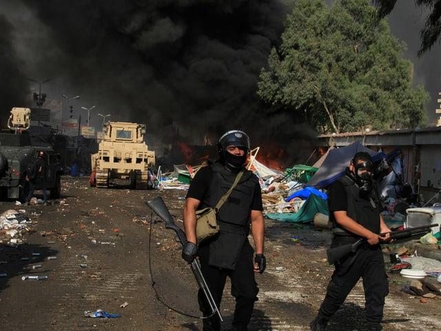 Zweil Polizisten in schwarzer Kleidung und mit Gasmaske. Im Hintergrund ein Militärfahrzeug und dichter, schwarzer Rauch.