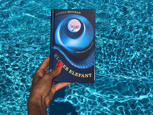 Annette König hält das Buch von Achmed Mourad: «Blauer Elefant» vor blaues Wasser