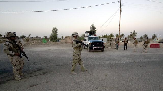 Soldaten mit Gewehren in der Wüste.