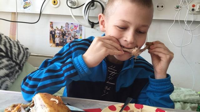 Mattia ist im Spitalbett und isst ein Poulet