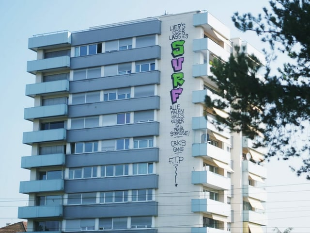 Basler Hochhaus; von oben nach unten hat jemand eine Botschaft gesprayt: Alle malen Halls, keiner ist mehr Strasse.