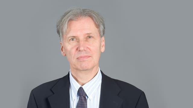 Mann mit grauem Haar in Anzug und Hemd mit Krawatte.