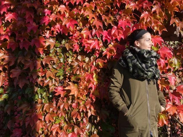 Die Autorin vor einer herbstlichen Wand mit Schal