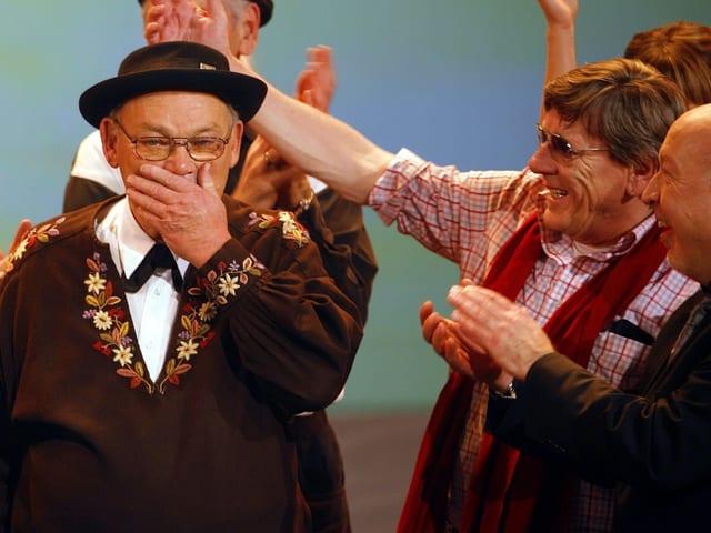Ruedy Rymann in Obwaldner Tracht wird von Polo Hofer auf Bühne bejubelt.