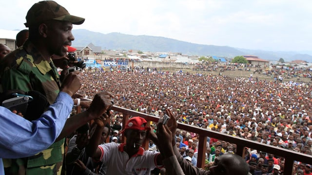 Ein Rebellensprecher steht auf einem Podest und spricht zu einer Menschenmenge.