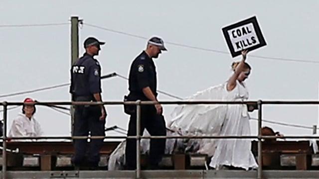 Eine Frau in einem weissen Kleid hält ein Schild «coal kills», sie wird von zwei Polizisten gefolgt.