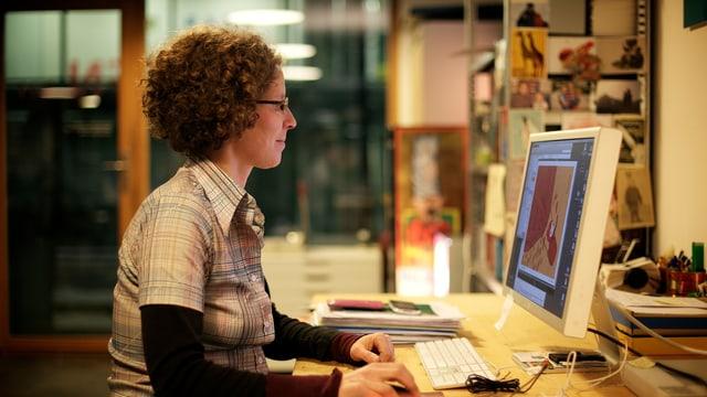 Die Illustratorin Judith Zaugg sitzt vor ihrem Computer.