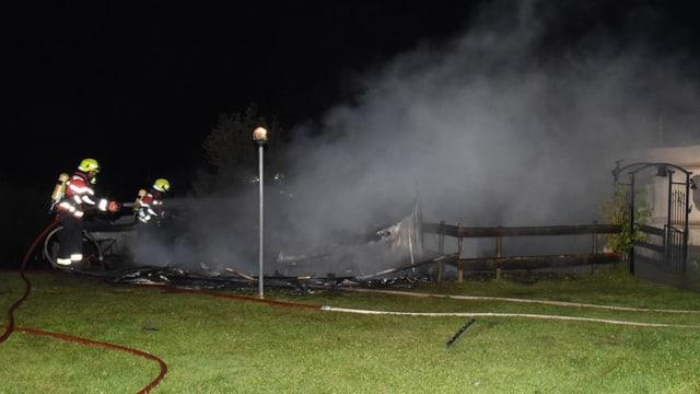 Feuerwehrleute bekämpfen einen Brand mit Wasserschläuchen im dichten Rauch.
