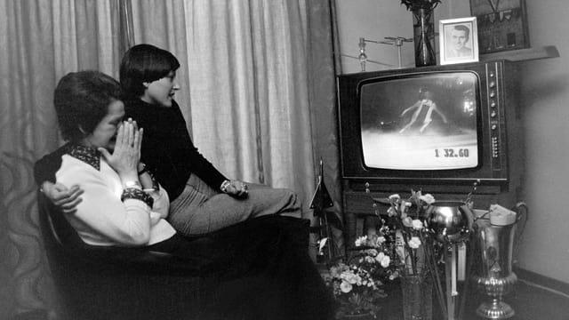 Schwarz-weiss-Aufnahme: Eine ältere und eine jüngere Frau sitzen gebannt vor dem Fernseher, in dem ein Skirennen läuft.
