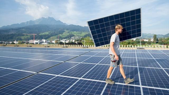 Ein Handwerker trägt ein Solarpanel über eine Solaranlage.