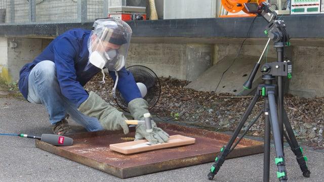 Mann mit Gesichtsschutz und Handschuhen treibt einen  Nagel durch den Akku.