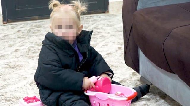 Spielendes Kind sitzt am Boden (Gesicht gepixelt).