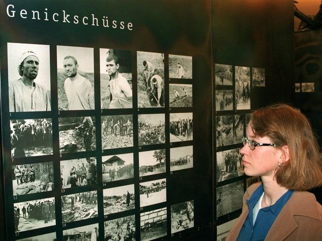 """Eine Frau betrachtet Fotos in einer KZ-Ausstellung. Die Tafel heisst """"Genickschüsse"""""""