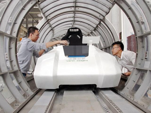 Zwei chinesische Ingenieure arbeiten an einem Bahnmodell