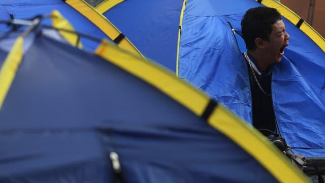 Ein Thailänder gähnt, während er aus dem Zelt schaut.