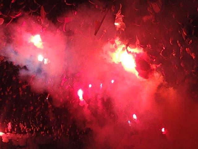 Fussballfans feiern ihre Mannschaft im roten Licht der Petarden.