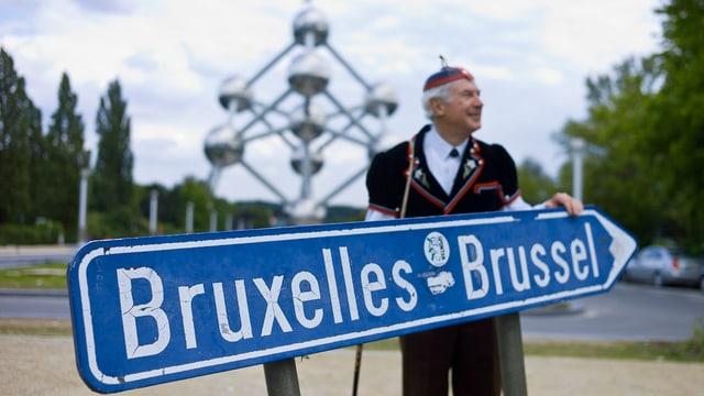 Symboldild: Erkennbarer Schweizer in Tracht steht hinter einem Brüssel-Wegweiser, im Hintergrund das Atomium.