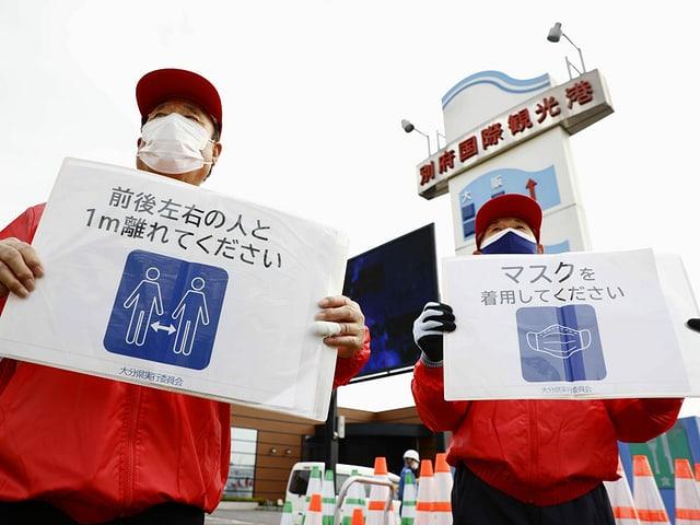 2 Japaner weisen auf die Corona-Regeln hin.