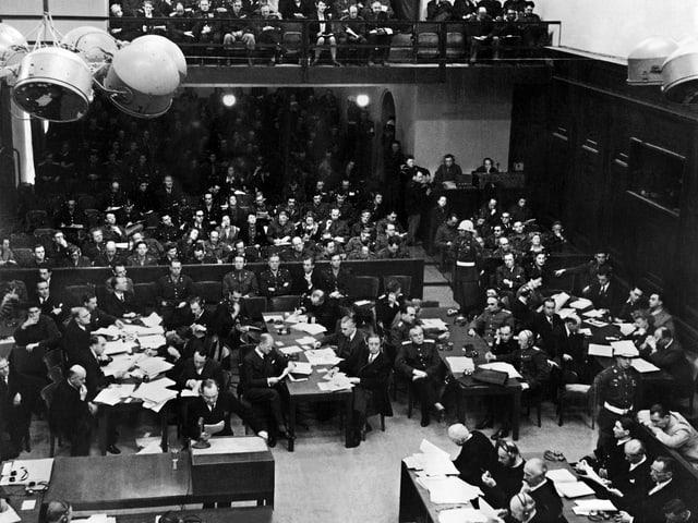 Gerichtssaal voller Menschen: Angeklagte, Richter, Ankläger und Verteidiger. Schwarz-weiss.