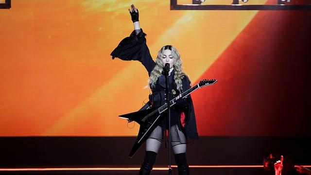 Madonna steht auf der Bühne. EIne Hand hällt ihre Gitarre, die andere streckt sxie in die Höhe.