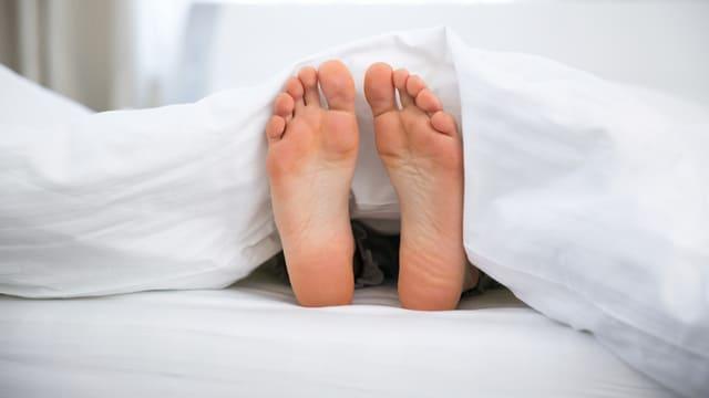 Nackte Füsse schauen unter der weissen Bettdecke hervor.