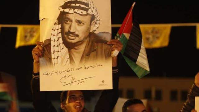 Palästinenser halten ein Plakat des früheren Palästinenserführers Jassir Arafat hoch.