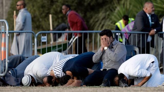 Purtret da muslims che fan oraziun giun plaun avant ina da las duas moscheas pertutgadas.