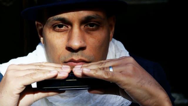 Ein Mann hält eine Mundharmonika in der Hand