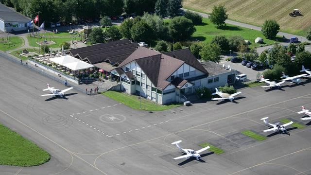 Flugplatzgebäude von oben. Auf der Pister Sportflugzeuge.